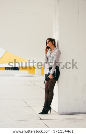 Trendy modern professional business woman talking on cellphone and holding digital tablet. Sexy businesswoman leaning on a wall on a working break outside corporate building. - stock photo
