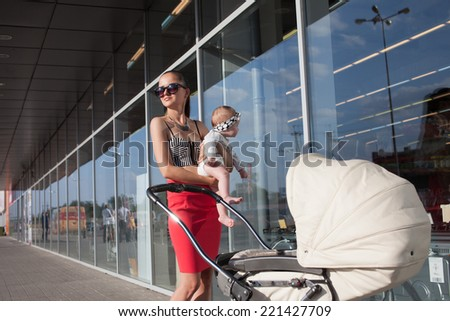 Trendy mother and baby posing near showcase - stock photo