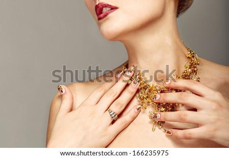 Trendy nail design and beautiful necklace of golden pins safe - stock photo