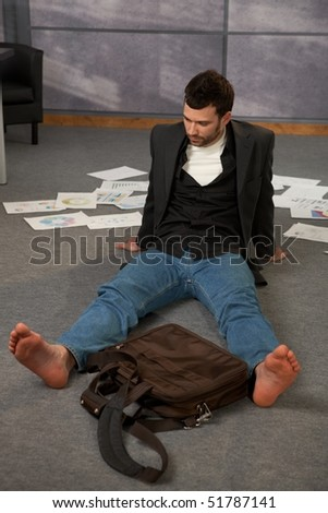 Trendy office worker sitting on office floor bare feet, surrounded with papers, documents and  laptop bag.