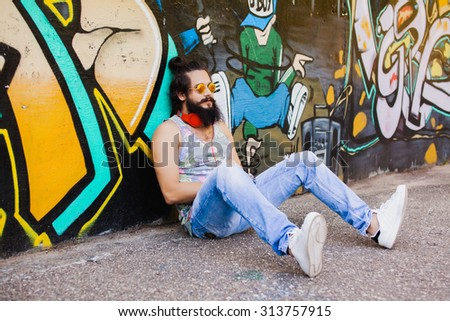 Trendy portrait of hipster  portrait.Stylish man posing with cool hairstyle,wall,ready to car trip.Happy and active.American street style,sportsman,young dj,t-shirt and shorts,Cool beard.big earphones - stock photo