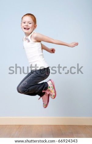 Trendy red-haired little girl jumping indoors - stock photo