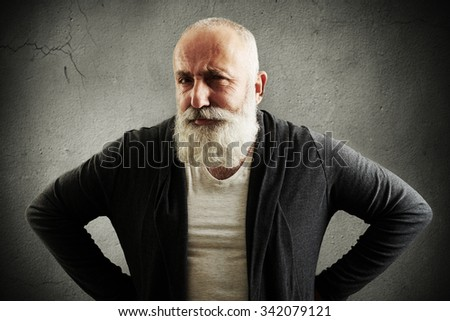 trendy senior man looking at camera with interest over dark grey wall - stock photo