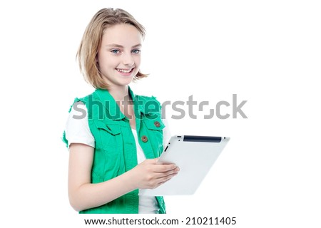 Trendy smiling young girl posing with her tablet computer - stock photo