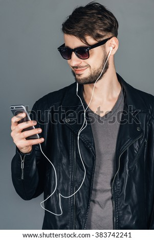 Trendy song. Confident young man in headphones looking at his smartphone with smile while standing against grey background - stock photo