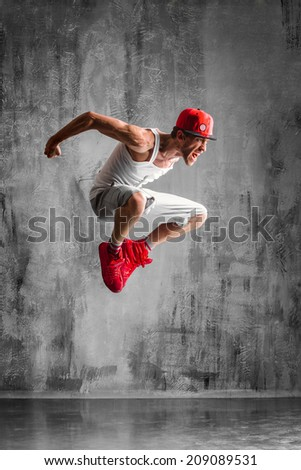 trendy style dancer jumping on studio background - stock photo
