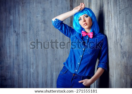 Trendy teen girl in bright blue wig and jeans clothes posing by a grunge wall. Beauty, fashion. - stock photo