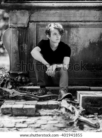Trendy teen hipster seated outside, black and white.