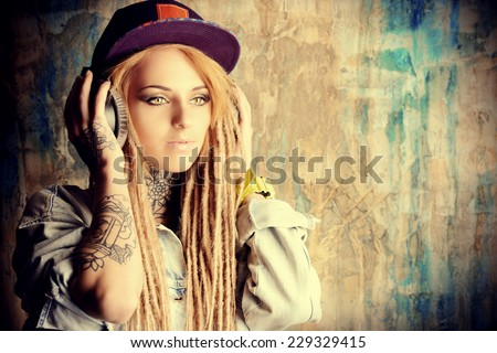 Trendy teenage girl with blonde dreadlocks listening to music on headphones. Jeans style. Modern generation. - stock photo
