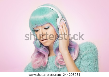 Trendy teenage girl with green and pink hair listening to music on headphones. Modern young fashionable woman in pastel colored fuzzy sweater looking down against pastel pink background. - stock photo