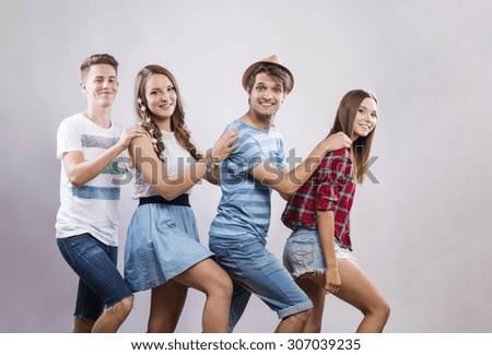 Trendy teenagers posing. Studio shot on gray background - stock photo