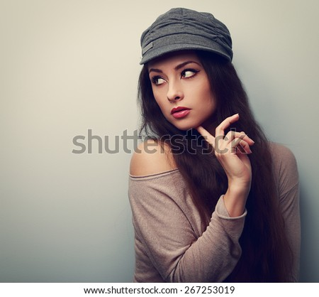 Trendy thinking young female  in cap looking. Vintage color portrait with empty copyspace. - stock photo