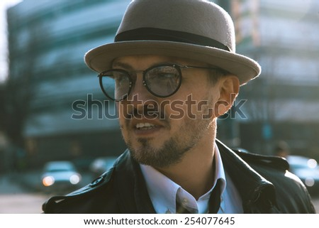trendy unshaven man in a hat and glasses looking aside outdoors