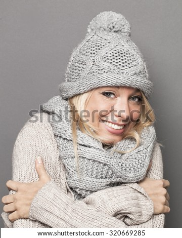 trendy warm winter - beautiful young blond woman trying to stay warm in wrapping up herself in gray wool winter hat and scarf for comfort and cozy temperature - stock photo