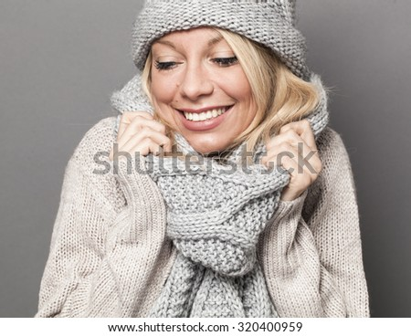 trendy warm winter - gorgeous young blond woman wrapping up herself in gray wool winter hat and scarf smiling for softness and cozy fashion - stock photo
