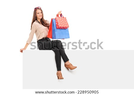 Trendy woman holding shopping bags seated on panel isolated on white background - stock photo