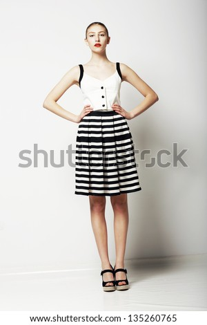 Trendy Woman in Stripped Skirt and T-Shirt standing. Urban Clothing Collection - stock photo