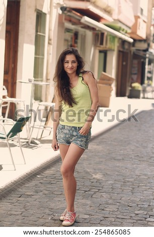 Trendy woman in summer shorts walking in the city. Vintage portrait