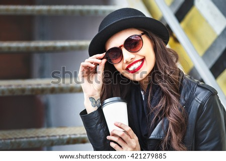 Trendy woman in sunglasses and hat  with drink sitting outdoor. Young  woman in sunglasses sitting near stairs in the street and holding cup of coffee - stock photo