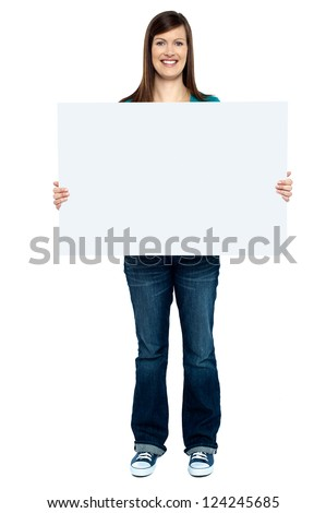 Trendy woman showing blank billboard to camera. Full length studio shot. - stock photo