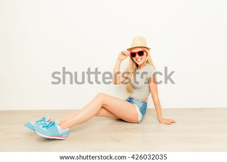 Trendy woman sitting on floor in summer hat and glasses - stock photo