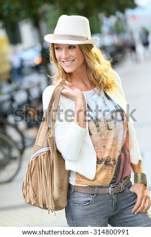 Trendy woman with hat walking in city street - stock photo