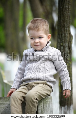 Trendy 2 years old baby boy posing in spring/autumn park - stock photo
