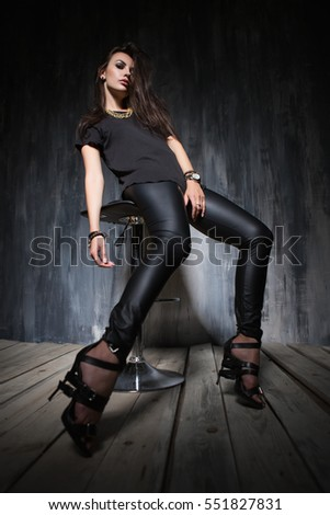 Trendy young brunette posing in black clothes