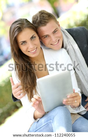 Trendy young couple in town using tablet - stock photo