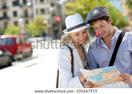Trendy young couple in town with touristic map - stock photo