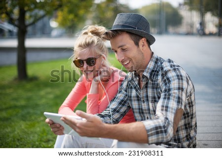 trendy young couple listening music on a digital tablet in the street - stock photo