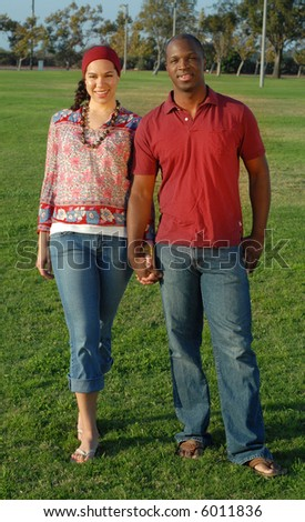 Trendy young couple standing outside in the park, holding hands - stock photo