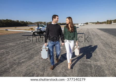 Trendy young couple walking from private plane with baggage - stock photo