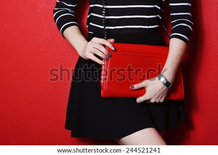 Trendy young girl in black skirt and striped shirt holding red leather handbag red background - stock photo