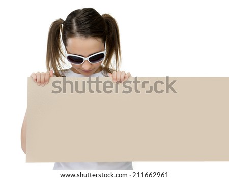 Trendy young girl in stylish sunglasses pointing to a blank card or sign that she is holding in front of her chest with copyspace for your text or advertisement, on white - stock photo