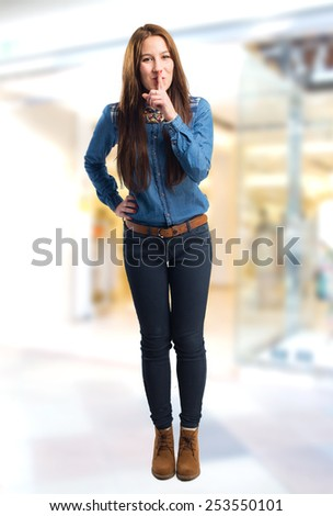 Trendy young woman doing the silence gesture. Over shopping center background - stock photo