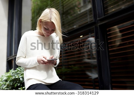 Trendy young woman focused chatting or talk on smart phone near blank copy space background for your content or text message, female hipster student using mobile phone for connect to wireless outdoors - stock photo