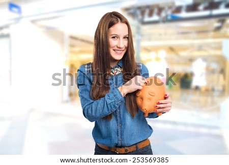 Trendy young woman holding a piggy bank. Over shopping centre background - stock photo
