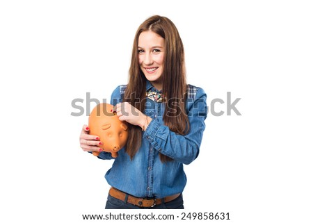Trendy young woman holding a piggy bank. Over white background - stock photo