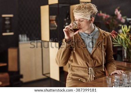 Trendy young woman in modern cafe with fresh coffee - stock photo