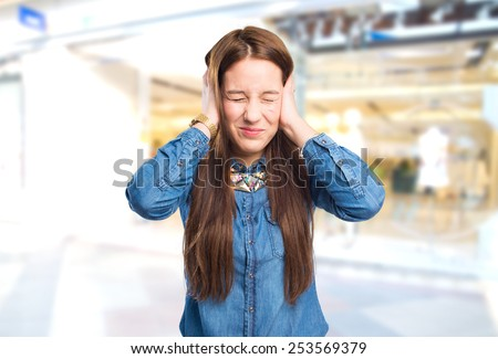 Trendy young woman looking annoyed because a noise. Over shopping centre background - stock photo