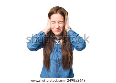 Trendy young woman looking annoyed because a noise. Over white background - stock photo