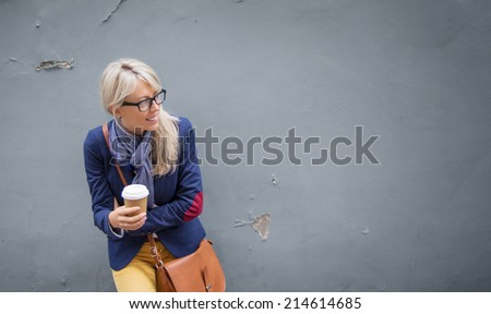 Trendy young woman standing at the wall outdoors and holding a cup of coffee. - stock photo