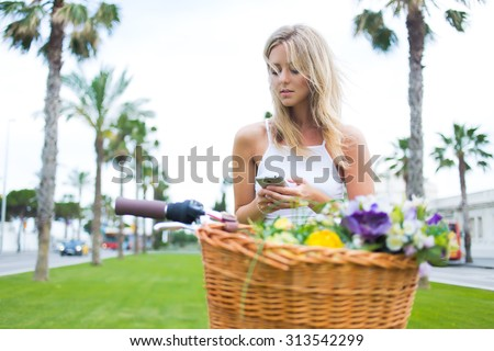 Trendy young woman stop to riding on her vintage bike with basket of flowers while focused chatting or talk on smart phone outside,gorgeous female using mobile phone during recreation time in the park - stock photo