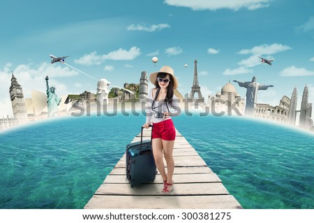 Trendy young woman travelling to the worldwide monument by carrying luggage and digital camera