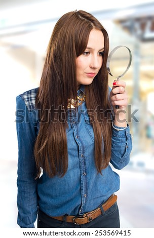 Trendy young woman using a magnifying glass. Over shopping centre background - stock photo