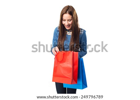 Trendy young woman with red and blue shopping bags. Over white background - stock photo