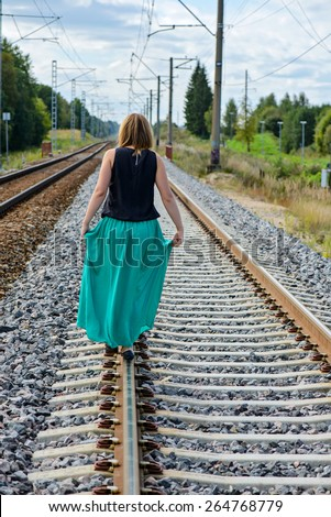 Trendy young women walking on the rail track - stock photo