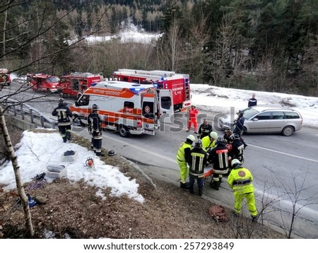 TRENTO, ITALY - MARCH 1, 2015: Paramedics and Firefighters tending to the first aid of an injured motorist at the scene of a car crash. Ambulance cars and rescuers on the road on March 2, 2015. - stock photo