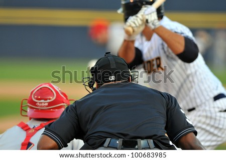 TRENTON, NJ - APRIL 21: A home plate umpire watches a ball come into the batter, catcher also in frame, during the Eastern League baseball game April 21, 2012 in Trenton, NJ. - stock photo